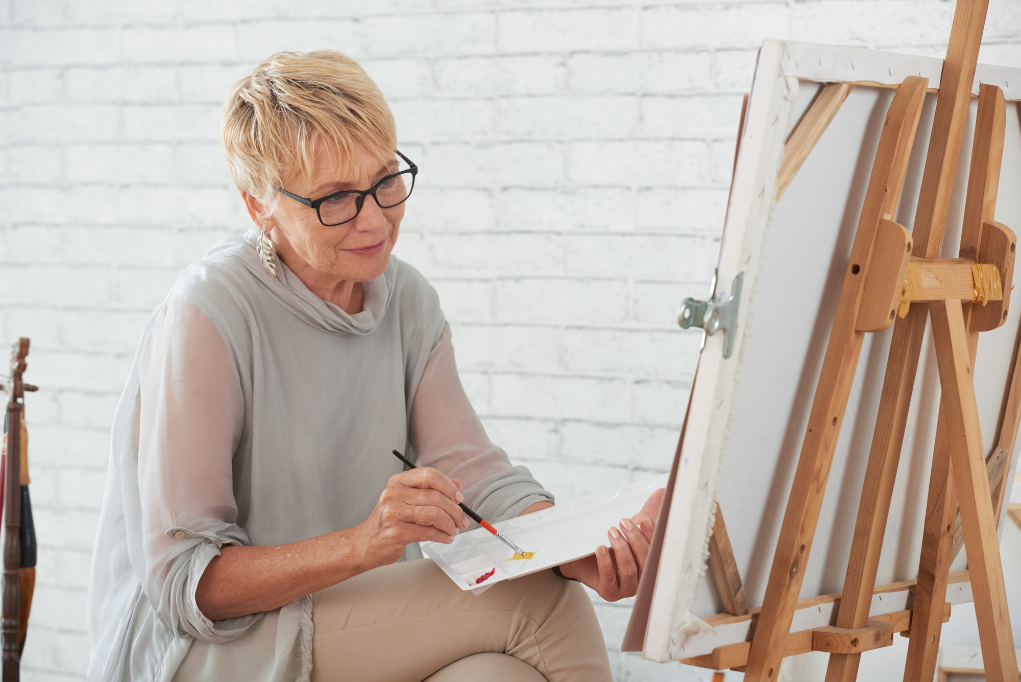 Senior woman painting at an easel. Art therapy offers significant benefits to both psychological and physical well-being.